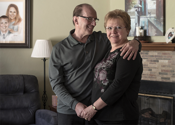 Vivian and Michael Scholze stand in their living room in Harrison City, Pa. In 2017, after taking ineffective medication for years, Vivian went to UPMC for a deep brain stimulation implant to relieve her essential tremor.