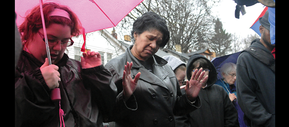 Mourners gather at a vigil on Franklin Ave. in Wilkinsburg, Pa., for mass shooting victims who were ambushed at a party in 2016. The death toll  included five adults and an 8-month-old fetus. Richard Garland, of the Graduate School of Public Health, acts as a mediator to try to prevent conflicts from turning deadly. (Photo: John Heller, © Pittsburgh Post-Gazette, 2019, all rights reserved. Reprinted with permission)
