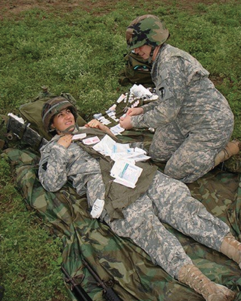 Kimberly Bell and a fellow Army National Guard recruit in a medic exercise during active duty training.