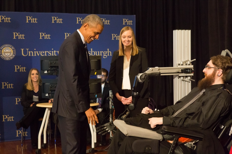 President Obama meets Nathan Copeland. (When they shook hands, Copeland used a robotic arm controlled with his thoughts. Through electrodes implanted in his sensory cortex, Copeland could feel the president's grip.) Researcher Jennifer Collinger stands by.